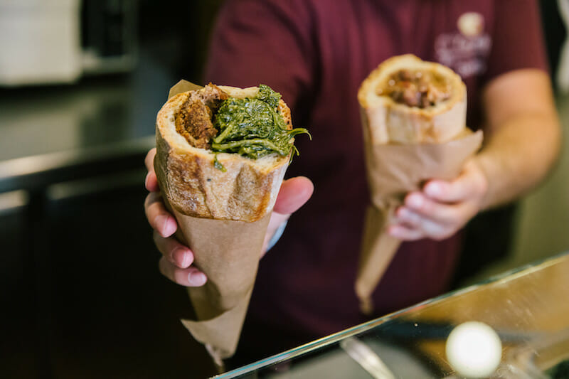 """NAPLES, ITALY - 11 JUNE 2019: A cuzzetiello filled with fried meatballs and friarelli (Neapolitan fried broccoli) is seen here at O' Cuzzetiello, a panini take away in Naples, Italy, on June 11th 2019.<br /> The cuzzetiello (bread bowl) is among the oldest and most traditional snacks in the city of Naples. It is made out of the """"cozzetto"""" (the extremities of the bread), emptied of the crumb and filled with a traditional Neapolitan side contour : ragù sauce, fried meatballs, eggplant parmigiana, sausage and friarelli, etc.<br /> """"O' Cuzzetiello"""" is a Cuzzetiello panic take-away founded by Dario Troise in 2016, who succeeded in creating a project that he had been caressing for at least 15 years: a panini bar that serves only sandwiches in the shape of the cuzzetiello."""