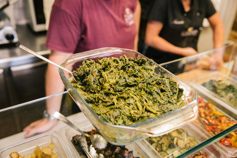 """NAPLES, ITALY - 11 JUNE 2019: Friarelli (fried Neapolitan broccolis) are seen here together with other Neapolitan side dishes used to fill the cuzzetiellos, here at O' Cuzzetiello, a panini take away in Naples, Italy, on June 11th 2019.<br /> The cuzzetiello (bread bowl) is among the oldest and most traditional snacks in the city of Naples. It is made out of the """"cozzetto"""" (the extremities of the bread), emptied of the crumb and filled with a traditional Neapolitan side contour : ragù sauce, fried meatballs, eggplant parmigiana, sausage and friarelli, etc.<br /> """"O' Cuzzetiello"""" is a Cuzzetiello panic take-away founded by Dario Troise in 2016, who succeeded in creating a project that he had been caressing for at least 15 years: a panini bar that serves only sandwiches in the shape of the cuzzetiello."""