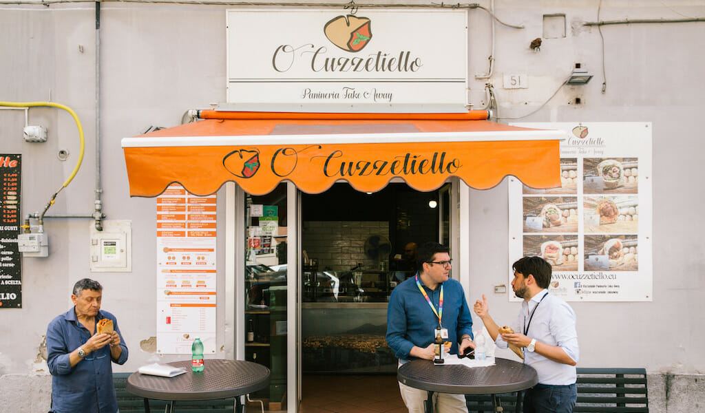 """NAPLES, ITALY - 11 JUNE 2019: Customers are seen here eating their cuzzetiellos at O' Cuzzetiello, a panini take away in Naples, Italy, on June 11th 2019.<br /> The cuzzetiello (bread bowl) is among the oldest and most traditional snacks in the city of Naples. It is made out of the """"cozzetto"""" (the extremities of the bread), emptied of the crumb and filled with a traditional Neapolitan side contour : ragù sauce, fried meatballs, eggplant parmigiana, sausage and friarelli, etc.<br /> """"O' Cuzzetiello"""" is a Cuzzetiello panic take-away founded by Dario Troise in 2016, who succeeded in creating a project that he had been caressing for at least 15 years: a panini bar that serves only sandwiches in the shape of the cuzzetiello."""