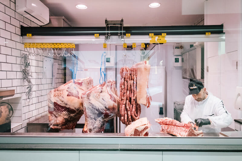 NAPLES, ITALY - 30 MAY 2019: A butcher is seen here at work at D'Ausilio, a butcher shop in Naples, Italy, on May 30th 2019.<br /> Raffaele D'Ausilio comes from a family of butchers. His grandfather, Alfredo d'Ausilio, opened a butcher shop in 1947. All four of his children became butchers, including Raffaele's father Vincenzo. In the early 2000s, Raffaele and his wife Roberta took over the family business with their touch of innovation: a butcher shop during the day, a take-away burger shop at night.