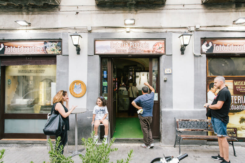 NAPLES, ITALY - 13 JULY 2019: Customers are seen here at the entrance of the Osteria Totò Eduardo e Pasta e Fagioli, a restaurant in Naples, Italy, on July 13th 2019.<br /> The name of the Osteria is dedicated to the two masters of Neapolitan theatre and cinema: Totò (Antonio de Curtis) and Eduardo de Filippo. The idea came from Mario Bianchini, an aficionado of Neapolitan culture who wanted to pay tribute to his wife Rosaria de Curtis, a distant relative of Totò, the most famous actor in the history of Naples.<br /> The osteria was founded in the 1970s by Mario Bianchini who wanted to base its menu on traditional Neapolitan dishes. Mr Bianchini learned the art of cooking from his mother Anna.